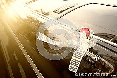 Door of black wedding car with flower