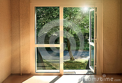 The door to summer. Sun-flooded room with an open door to the street. Stock Photo