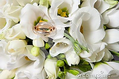 Anillos de bodas en el ramo hermoso de freesias blancos