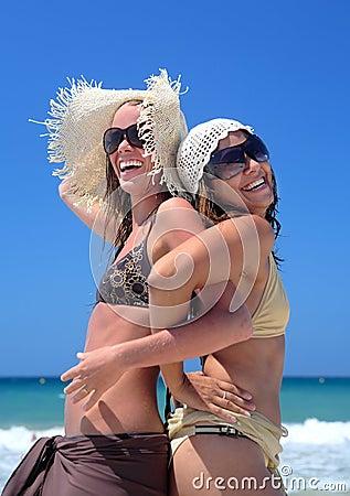Dos chicas jóvenes o amigos atractivos que juegan en una playa asoleada en vaca