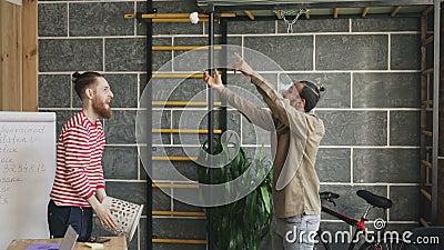 Dos colegas se divierten que juega el papel que lanza del juego de baloncesto en compartimiento de los desperdicios en oficina mo almacen de video