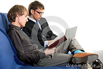 Dos estudiantes con el cuaderno y la computadora portátil.
