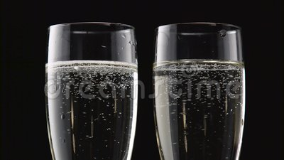 Dos flautas de vino espumoso enfriado Bokeh que centella el fondo negro Cierre para arriba almacen de metraje de vídeo
