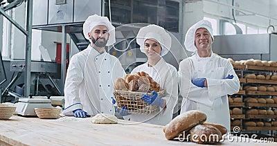 Dos generaciones de panaderos dos hombres y mujeres en una gran panadería mirando directamente a la cámara y sonriendo al lado almacen de metraje de vídeo