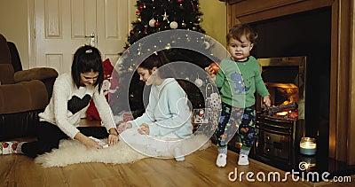 Dos hermanas felices que adornan el árbol de la Navidad y del Año Nuevo e hijo lindo que come la manzana y que mira in camera cer almacen de metraje de vídeo