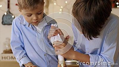Dos hermanos están decorando una galleta navideña con una bolsa de pastelería en la cocina de casa almacen de video