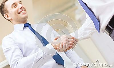 Dos hombres de negocios que sacuden las manos en oficina
