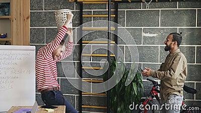 Dos hombres multirraciales se divierten que juega el papel que lanza del juego de baloncesto en compartimiento de los desperdicio metrajes