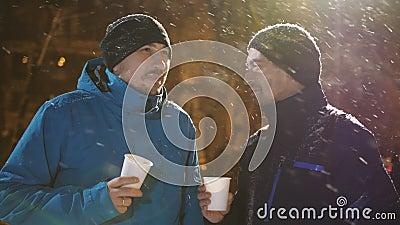 Dos hombres por la tarde en invierno en la calle que hablan y café de consumición ?l el nevar del ` s almacen de metraje de vídeo