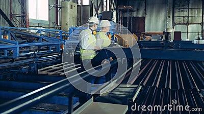 Dos ingenieros observan el transportador con baldosas metálicas almacen de metraje de vídeo