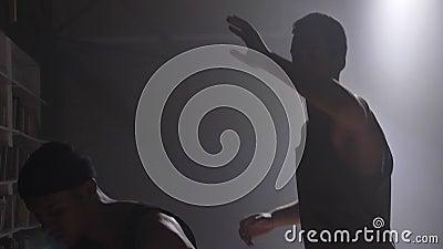 Dos jugadores de básquet sombrean jugar uno en uno dentro en sitio con humo y iluminado con focos almacen de video