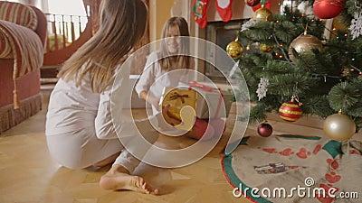 Dos muchachas alegres que corren a los regalos debajo del árbol de navidad en la mañana almacen de metraje de vídeo