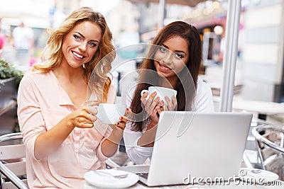 Dos muchachas hermosas en café con el ordenador portátil