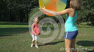 Dos muchachas lindas de diversas edades juegan con una bola inflable del arco iris colorido grande almacen de video