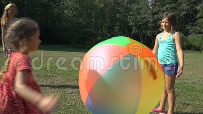 Dos muchachas lindas de diversas edades que su madre juega con una bola inflable del arco iris colorido grande metrajes