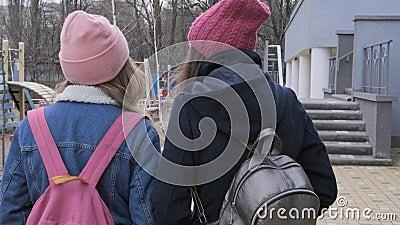 Dos muchachas que caminan, adolescentes en los casquillos, capas, chaquetas con las mochilas, opinión de la parte posterior almacen de video