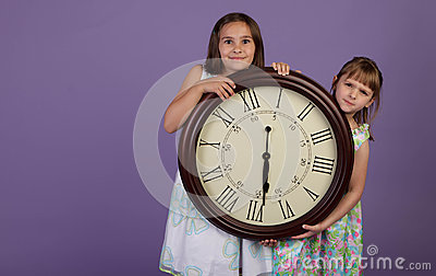 Dos muchachas que sostienen un reloj de pared grande
