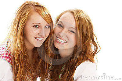 Dos muchachas vestidas bávaras del redhead feliz