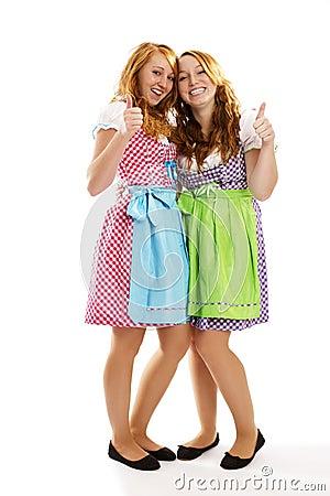 Dos muchachas vestidas bávaras felices que muestran los pulgares para arriba