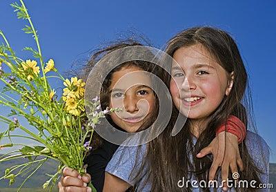Dos muchachas y flores amarillas