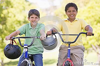 Dos muchachos jovenes en las bicicletas al aire libre que sonríen