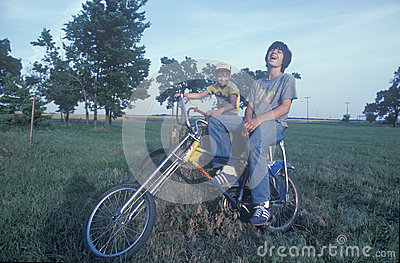 Dos muchachos que se sientan en sus bicis Foto editorial