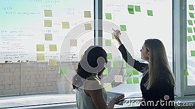 Dos mujeres de negocios en el fondo de la ventana en pasillo discuten temas metrajes