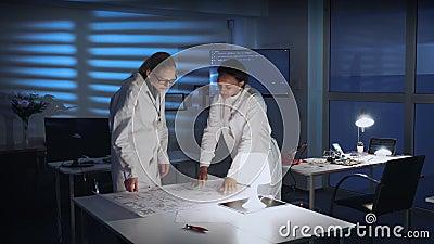 Dos mujeres elegantes en las capas del laboratorio que se encuentran para mejorar el esquema de la electrónica de control metrajes
