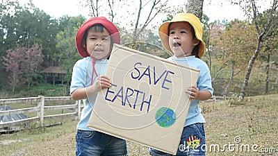Dos niñas hermanas sostienen un cartel que muestra un cartel que protesta contra la contaminación de plástico en el bosque almacen de video