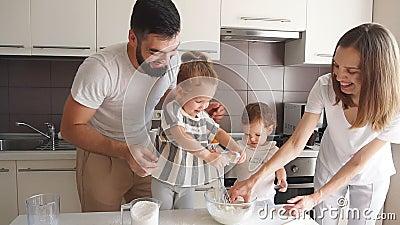 Dos niñas pequeñas ayudando a los padres a hacer pasta almacen de video