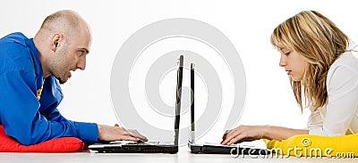 Dos personas que trabajan en las computadoras portátiles