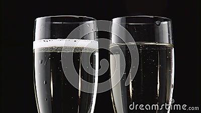 Dos vidrios transparentes de champán enfriado Bokeh que centella el fondo negro Cierre para arriba almacen de metraje de vídeo