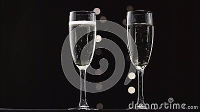 Dos vidrios transparentes de vino espumoso enfriado Bokeh que centella el fondo negro metrajes