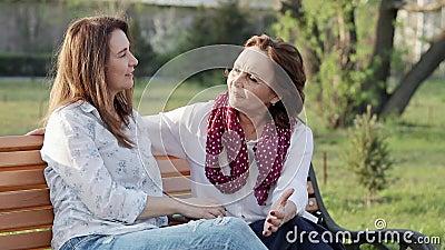 Dos viejas y de mediana edad novias felices atractivas de las mujeres que charlan en el parque almacen de video