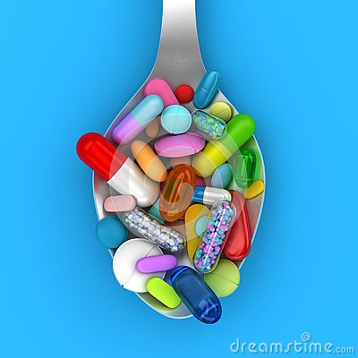 Dose of colorful pills in spoon Stock Photo