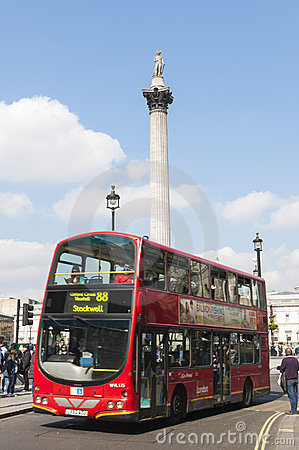 Double-decker bus driving by Trafalgar Square Editorial Stock Image