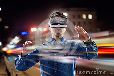 Double exposure, man wearing virtual reality goggles, night city Stock Photo