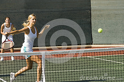 Doubles Player Hitting Tennis Ball With Backhand
