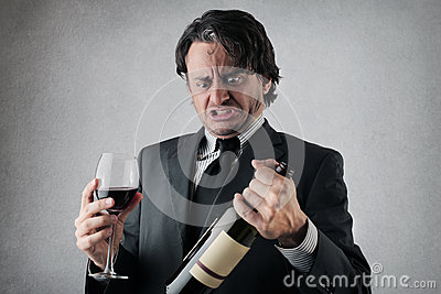Doubtful businessman with a glass and a bottle of wine