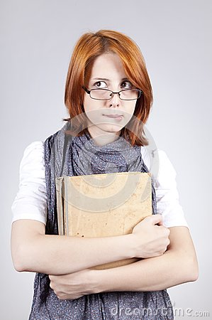 Doubting fashion girl in glasses with old book