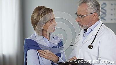 Doutor idoso que fala ao paciente fêmea que mostra resultados, doença, maneira do tratamento vídeos de arquivo