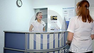 Doutor novo Talking com o paciente na mesa de recepção do hospital filme