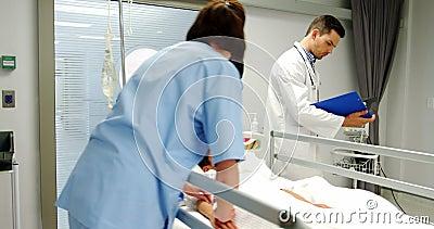 Doutores que colocam uma máscara de oxigênio e que ajustam um gotejamento do iv ao paciente nas urgências video estoque