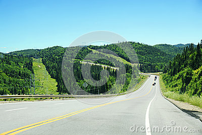 Downhill road with mountains and coniferous trees