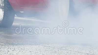 Drag car burnout. Fiery red drag strip muscle car burning rear wheel rubber while creating white smoke. Also showing a stationary front wheel, and finally stock video