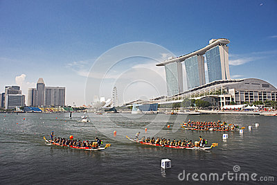 Dragon boats streaming into finish with MBS as backdrop Editorial Stock Image