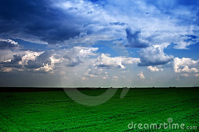 Dramatic cloudy sky and green field