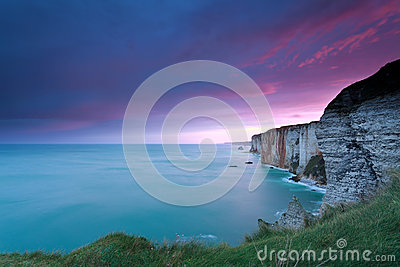 Dramatic fire sunrise over cliffs in ocean