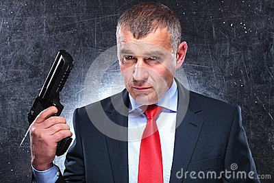 Dramatic picture of an old assassin holding his gun