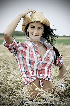 Dramatic portrait of pretty cowgirl in wheat field